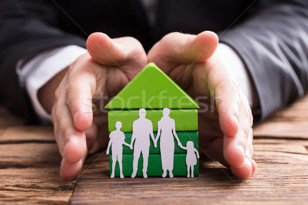 Stock photo: Businessperson Protecting House Model And Family Paper Cut Out