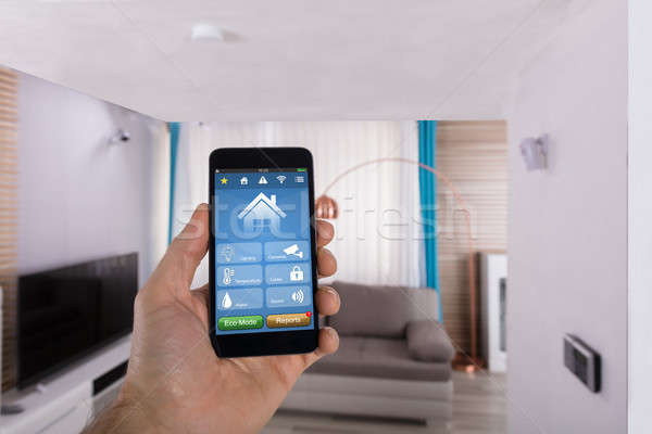 Human Hand Using Smart Home System On Smartphone Stock photo © AndreyPopov