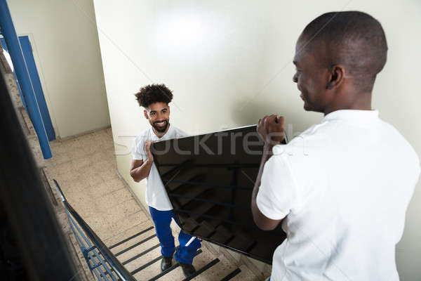 Young Movers Carrying Television While Climbing Steps Stock photo © AndreyPopov