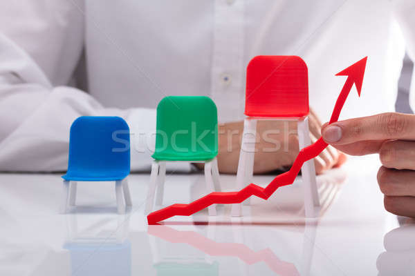 Chairs Behind Businessman Showing Arrow In Upward Direction Stock photo © AndreyPopov