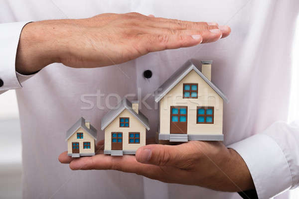 Businessman protecting increasing size of house models Stock photo © AndreyPopov