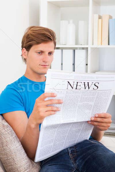 Homem sessão sofá leitura jornal moço Foto stock © AndreyPopov