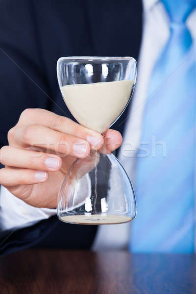 Businessman Holding Hourglass Stock photo © AndreyPopov