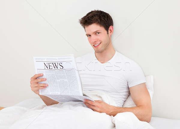 Férfi olvas újság fiatal jóképű férfi ágy Stock fotó © AndreyPopov