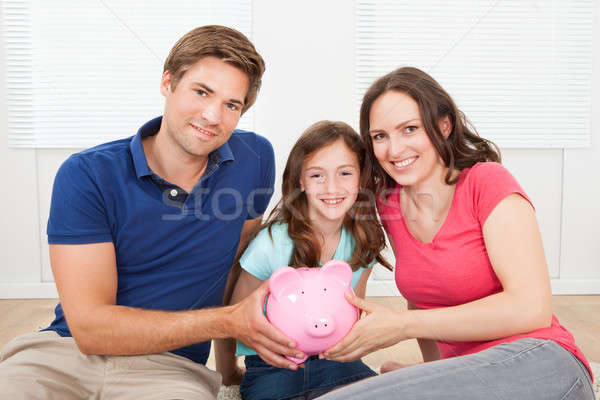 Happy Family Holding Piggy Bank At Home Stock photo © AndreyPopov