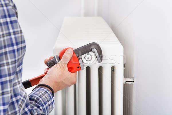 Vízvezetékszerelő megjavít radiátor közelkép férfi franciakulcs Stock fotó © AndreyPopov