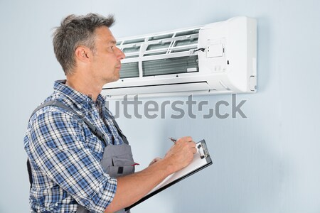 Man Holding Remote Controller Of Air Conditioner Stock photo © AndreyPopov
