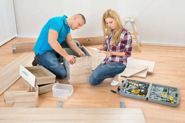 Couple Assembling Wooden Drawers Stock photo © AndreyPopov