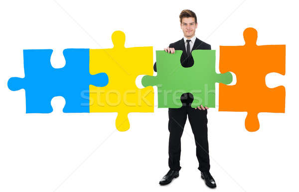 Confident Businessman Solving Jigsaw Puzzle Stock photo © AndreyPopov