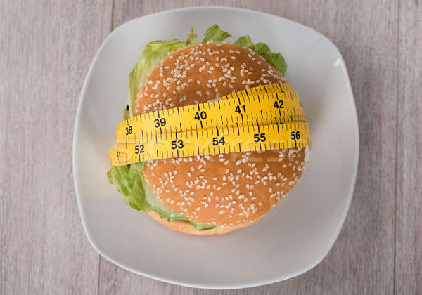 Burger Wrapped In Measure Tape On Plate Stock photo © AndreyPopov