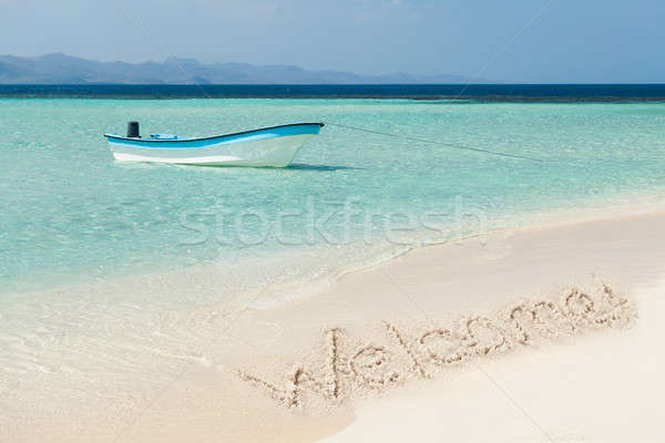 Boat Moored On Sea With Welcome Text Drawn On Sand Stock photo © AndreyPopov
