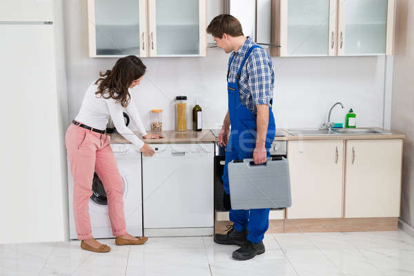 Woman Showing Dishwasher To Worker Stock photo © AndreyPopov