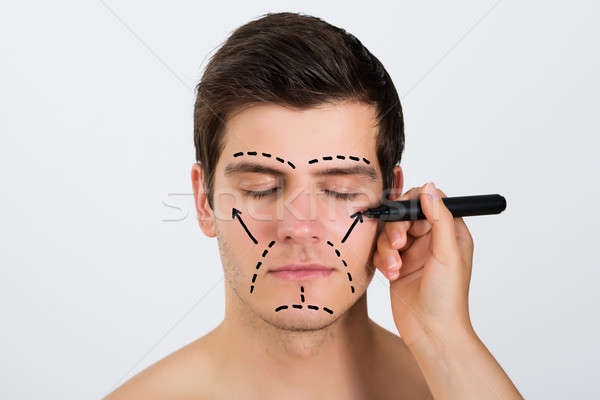 Person Hands Making Lines On Face Of Man Stock photo © AndreyPopov