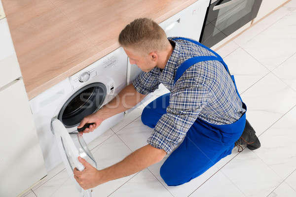 Worker In Overall Fixing Washer Stock photo © AndreyPopov