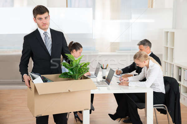 Stock photo: Businessman Carrying Belongings While Other People Working