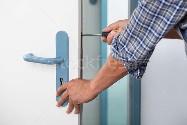 Technician Fixing Lock In Door With Screwdriver Stock photo © AndreyPopov