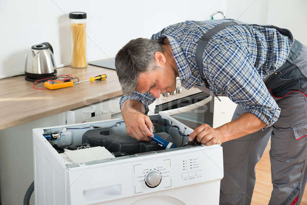 Stock photo: Handyman Checking Washing Machine With Flashlight