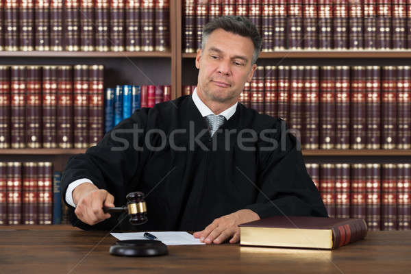 Confident Judge Striking The Gavel At Table Stock photo © AndreyPopov
