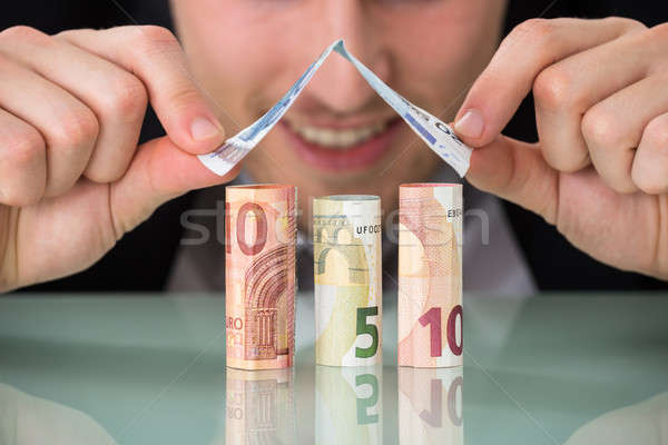Businessman Making House Of Banknotes Stock photo © AndreyPopov