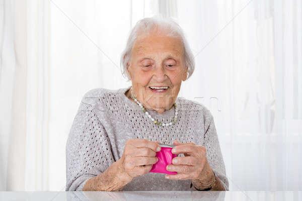 Idős nő tart kicsi pénztárca portré Stock fotó © AndreyPopov