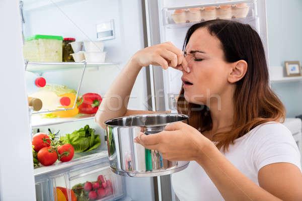 Woman Holding Foul Food Near Refrigerator Stock photo © AndreyPopov