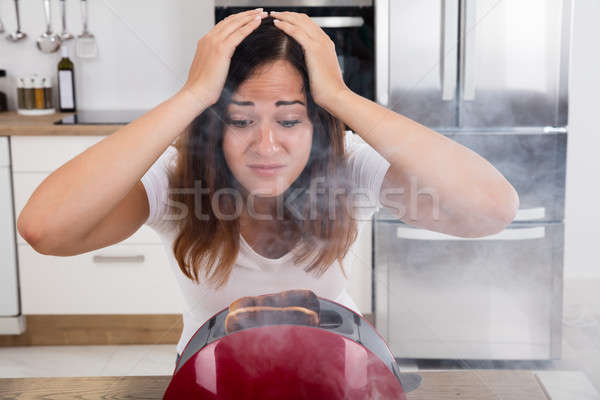 Frustrated Woman Looking At Burnt Toast In Toaster Stock photo © AndreyPopov