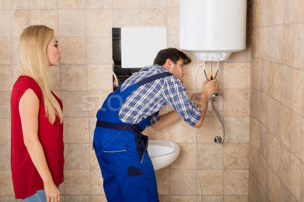 Male Worker Fixing Electric Boiler With Screwdriver Stock photo © AndreyPopov