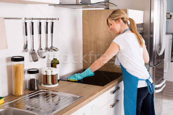 Woman Cleaning Induction Stove In Kitchen Stock photo © AndreyPopov