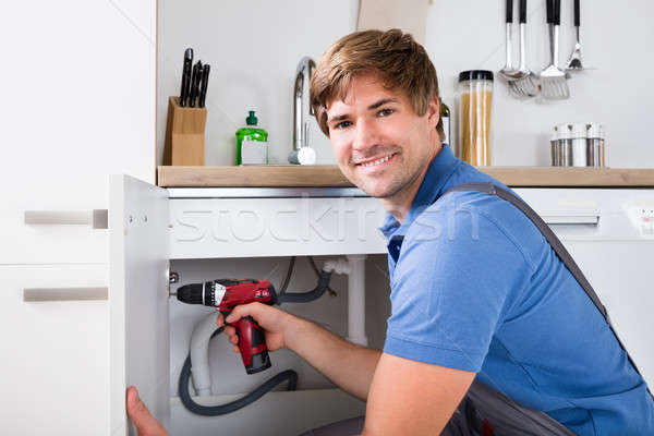 Young Male Handyman Fixing Cabinet Stock photo © AndreyPopov