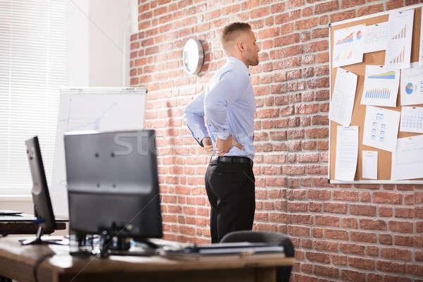üzletember hátfájás iroda dől téglafal papír Stock fotó © AndreyPopov
