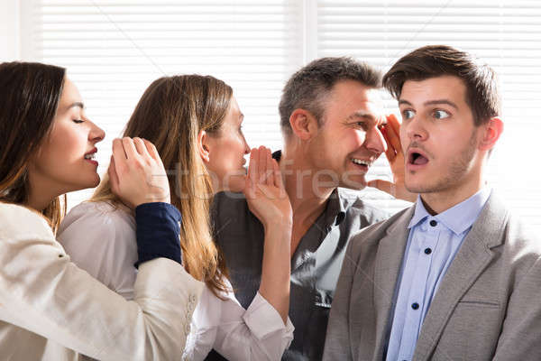 Stock photo: Secretive Business Colleagues Whispering In The Office