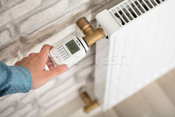 Person Adjusting Temperature On Thermostat Stock photo © AndreyPopov