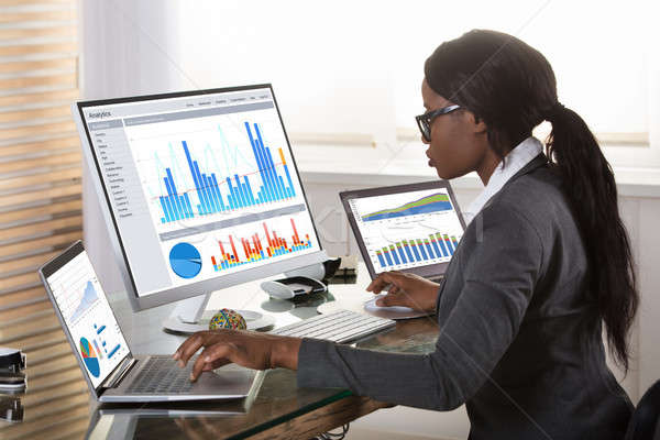 Businesswoman Looking At Graphs On Computer Stock photo © AndreyPopov