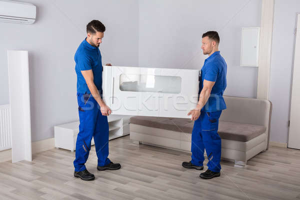 Two Movers Holding Furniture In Living Room Stock photo © AndreyPopov