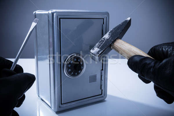 Thief Using Screwdriver And Hammer To Open Safe Stock photo © AndreyPopov