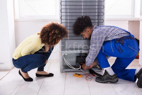Technician Examining Refrigerator With Digital Multimeter Stock photo © AndreyPopov