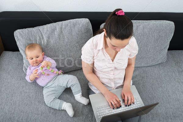 Nő laptopot használ ül kanapé baba játszik Stock fotó © AndreyPopov