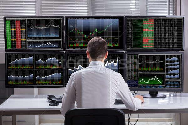 Mercado de ações corretor gráficos computador vista lateral jovem Foto stock © AndreyPopov