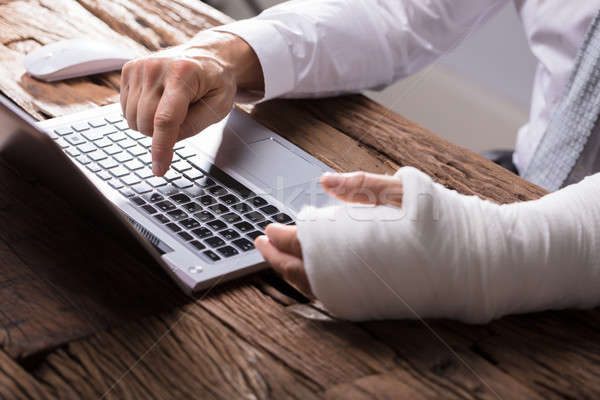 Stock photo: Businessperson With Hand Injury Using Laptop