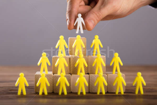 Person Placing White Human Figure Standing On Top Stock photo © AndreyPopov