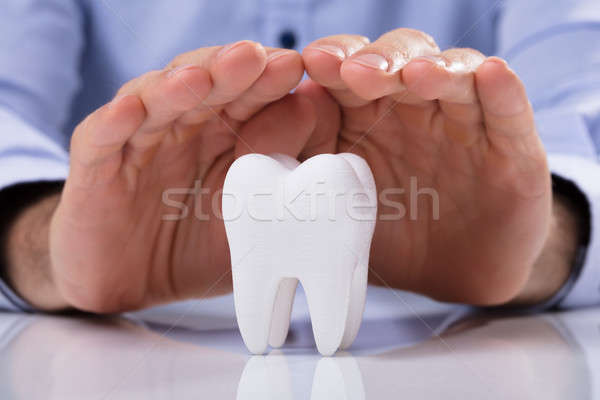 Man's Hand Protecting White Tooth Stock photo © AndreyPopov