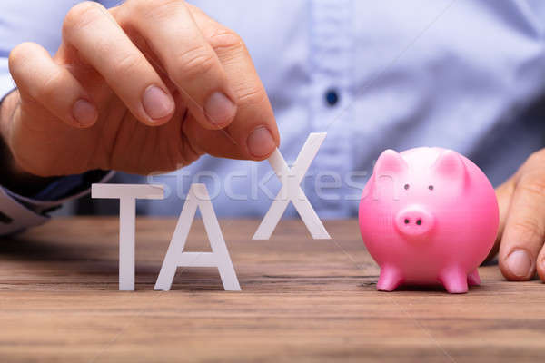 Human Hand Picking X Alphabet From Tax Word Stock photo © AndreyPopov