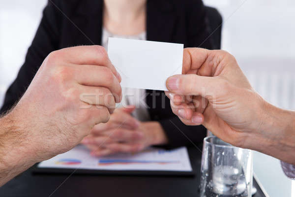 Exchanging Visiting Card In Front Of Colleague At Office Desk Stock photo © AndreyPopov