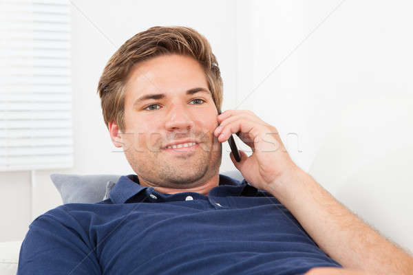 Smiling Man Answering Smart Phone At Home Stock photo © AndreyPopov