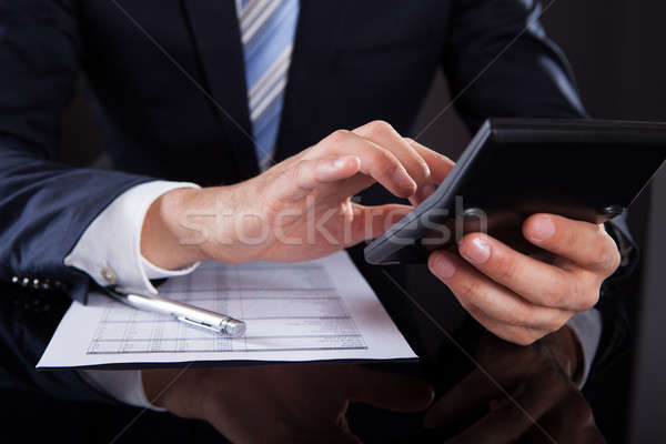 Businessman Using Calculator While Checking Expenses At Desk Stock photo © AndreyPopov