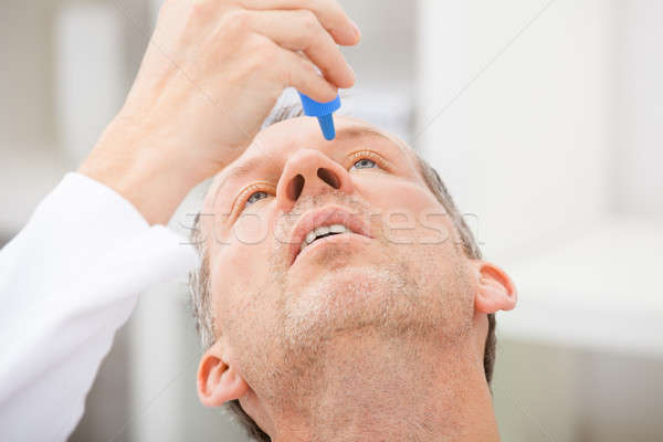 Mature Man Putting Eye Drops In Eyes Stock photo © AndreyPopov