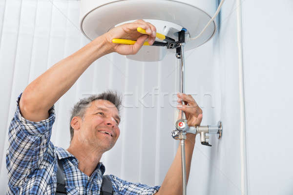 Male Plumber Repairing Electric Boiler Stock photo © AndreyPopov