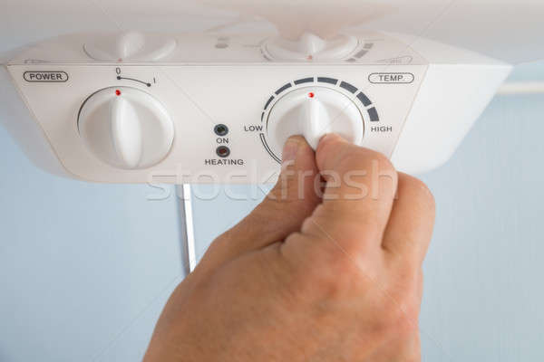 Person Adjusting Temperature Of Electric Boiler Stock photo © AndreyPopov