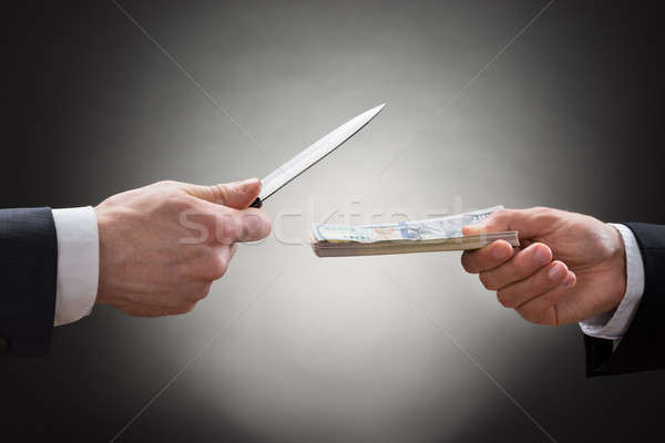 Businessman Giving Money To The Businessperson With Knife Stock photo © AndreyPopov