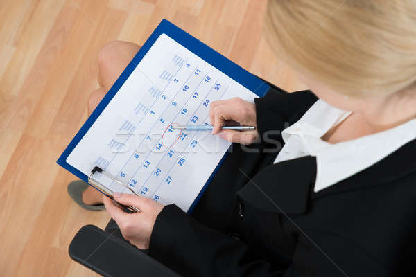Businesswoman Marking Date On Calendar Stock photo © AndreyPopov